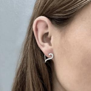 En kvinde med en ørering i sølv med hvide zirkoner fra Sif Jakobs Valentine kollektionen